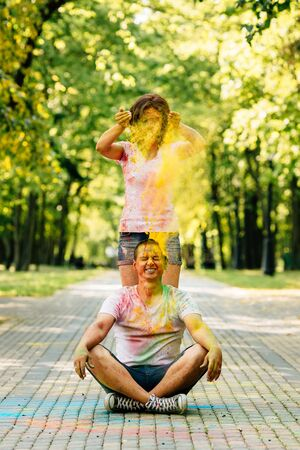 Young and beautiful, hipster couple funny playing in the park on holi color festival with colour paint powder. Dressed in white T-shirts and denim shorts. Girl throws paint on the guys head.