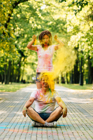 Young and beautiful, hipster couple funny playing in the park on holi color festival with colour paint powder. Dressed in white T-shirts and denim shorts. Girl throws paint on the guy's head.