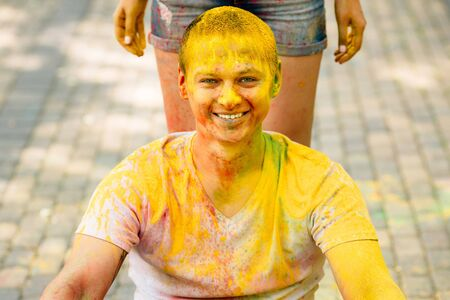 Young hipster man laughing happily at camera in the park on holi color festival. Dressed in white T-shirt.