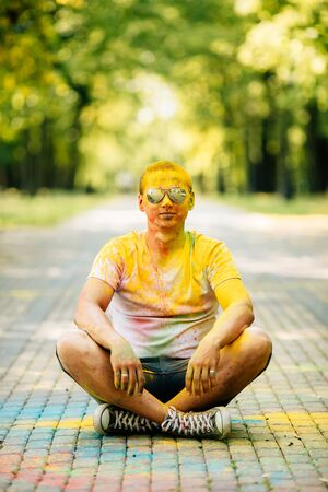Young hipster man laughing happily at camera in the park on holi color festival. Dressed in white T-shirt and denim shorts.