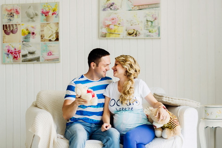 Couple dressed in blue and white colors with pregnant woman relaxing on white sofa in white room together. They are funny playing with bears.
