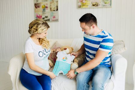 Young pregnant woman with husband on white sofa in white room lovely looking at baby clothes. Couple dressed in blue and white colors.