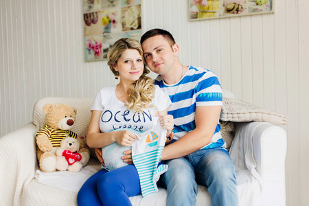 Young pregnant woman with husband on white sofa in white room with baby clothes. Couple dressed in blue and white colors.