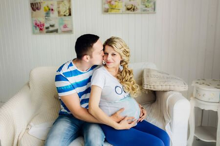 Couple dressed in blue and white colors with pregnant woman relaxing on white sofa in white room together. They are lovely hugging with hands on tummy.