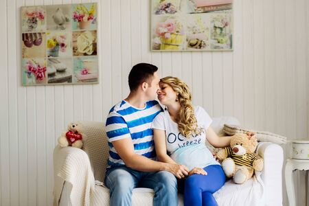 Couple dressed in blue and white colors with pregnant woman relaxing on white sofa in white room together. They are lovely hugging.