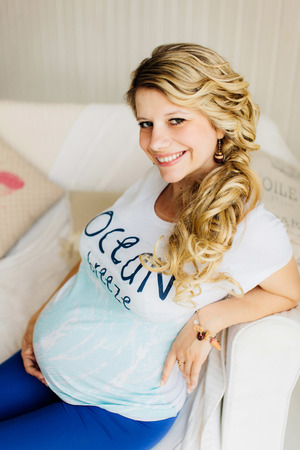 Young beautiful pregnant woman sitting on white sofa and lovely smiling. Blue and  white colors.