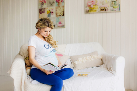 Young beautiful pregnant woman sitting on white sofa with a book.. Blue and  white colors.