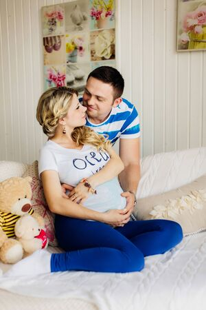 Pregnant beautiful woman with her handsome husband sweetly resting indoors on white sofa in white room together. Couple dressed in blue and white colors. They are lovely hugging with hands on tummy.