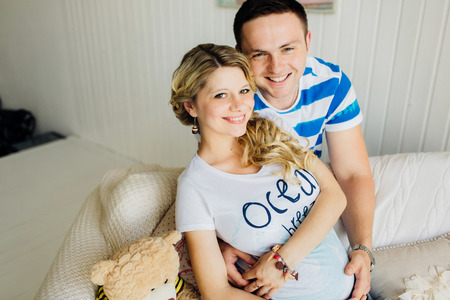 Portrait of expecting couple laughing happily at camera, embracing baby in belly together. Couple dressed in blue and white colors.