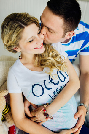 Portrait of expecting couple laughing happily, embracing baby in belly together. Couple dressed in blue and white colors.