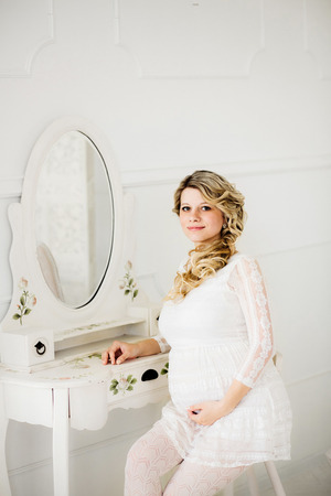 Young beautiful pregnant woman in white dress sitting on white chair in front of a mirror of boudoir table and lovely smiling in white room.