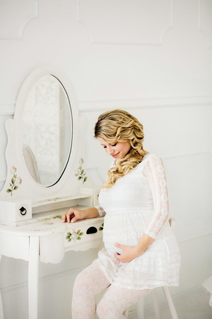 Young beautiful pregnant woman in white dress sitting on white chair in front of a mirror of boudoir table and lovely looking at belly in white room. Фото со стока