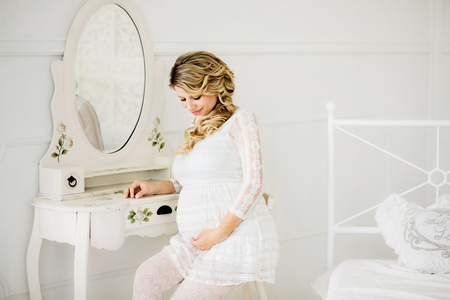 Young beautiful pregnant woman in white dress sitting on white chair in front of a mirror of boudoir table and lovely looking at belly in white room. Stockfoto