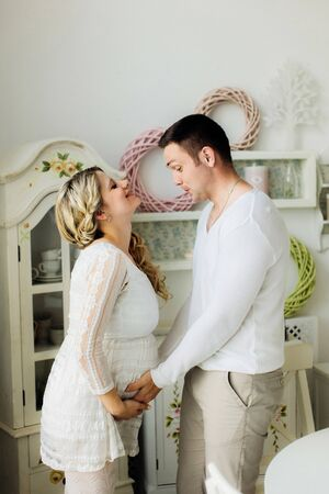 Happy young pregnant wife with husband dressed in white clothes lovely touching belly at home. Sensual photo.