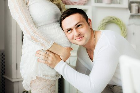 Happy husband with opened eyes listening to his pregnant wife belly at home. Couple dressed in white clothes. Sensual photo.