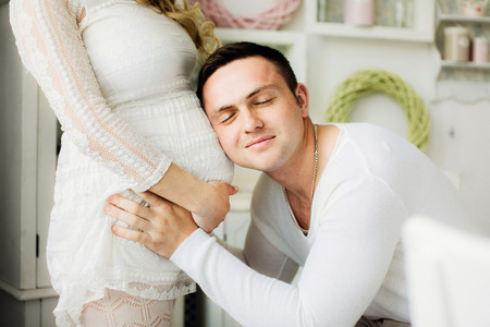 Happy husband with closed eyes listening to his pregnant wife belly at home. Couple dressed in white clothes. Sensual photo.