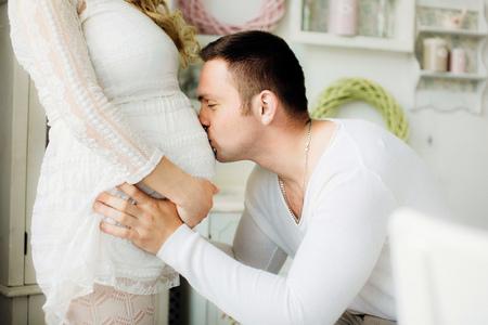 Close up von einem glücklichen Mann den Bauch seiner schönen schwangeren Frau küssen im weißen Schlafzimmer stehen. Paar in weiß gekleidet. Sensual Foto.