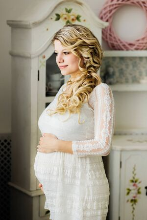 Beautiful pregnant woman in white dress caressing her belly in white room. Sensual photo.