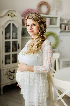 Beautiful pregnant woman in white dress caressing her belly in white room and looking at the camera. Sensual photo. Zdjęcie Seryjne