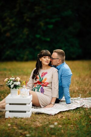 A pregnant beautiful woman with her handsome husband sweetly resting outdoors in the autumn on picnic on checkered blanket.