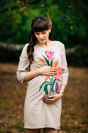 Beautiful pregnant woman is standing lovely on the yellow lawn with her hand on belly and looking at the tummy.