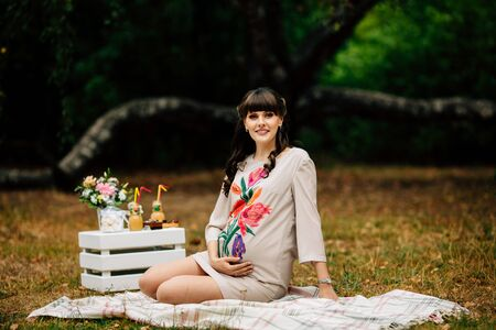 Beautiful pregnant woman holds pregnant tummy in nature in the autumn park on the checkered blanket.