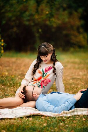 Handsome husband lying on his young pregnant beautiful womans leg in park. They are sweetly resting outdoors in the autumn on picnic.