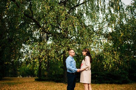 Pregnant beautiful woman and her handsome husband lovely relaxing, hugging on nature and have picnic in autumn park. Happy pregnant couple family. Healthy pregnancy.