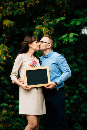 Expecting pregnant happy stylish couple holding a blank charcoal board. They are sweet kiss.