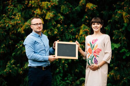 Expecting pregnant happy stylish couple holding a blank charcoal board. 스톡 콘텐츠
