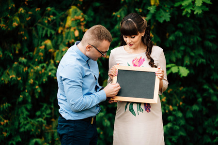 Expecting pregnant happy stylish couple holding a blank charcoal board.  Husband writes something.