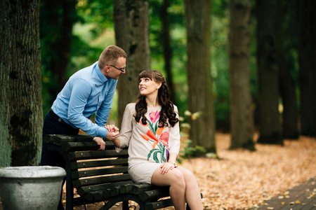Beautiful pregnant stylish couple relaxing outside in the autumn park sitting on bench. Handsome husband holds his wife's hand.