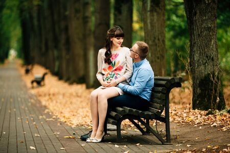 Beautiful pregnant stylish couple relaxing outside in the autumn park sitting on bench. They are lovely looking into each others eyes. Zdjęcie Seryjne