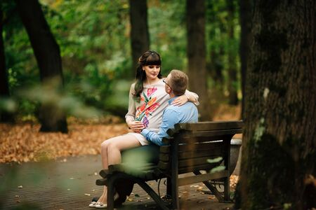 Beautiful pregnant stylish couple relaxing outside in the autumn park sitting on bench. They are lovely looking into each other's eyes. Stockfoto