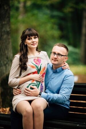 Beautiful and happy pregnant stylish couple relaxing outside in the autumn park sitting on bench.
