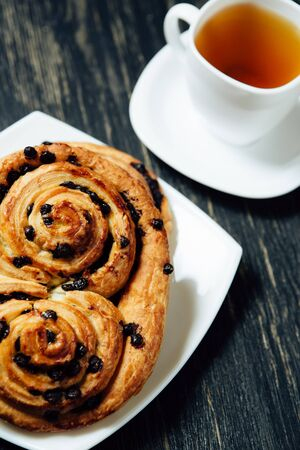 Tea and delicious homemade bakery with chocolate on dark wooden table. 스톡 콘텐츠