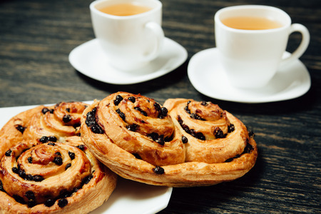 Tasty pretzels and two cups of tea on dark wooden table.