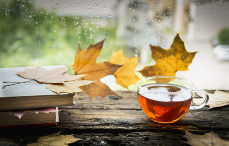 cup of tea on a wooden window sill with books and autumn leaves on a natural background
