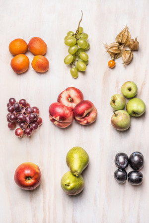 overhead view: heaps of fresh summer fruits on  white wooden background, top view Stock Photo