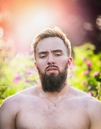 hombre escalera: Young man with beard  and straight face on sunset nature background, , close up