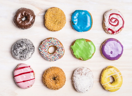 Glazed colorful doughnuts with  sprinkles and icing on white wooden background, top view