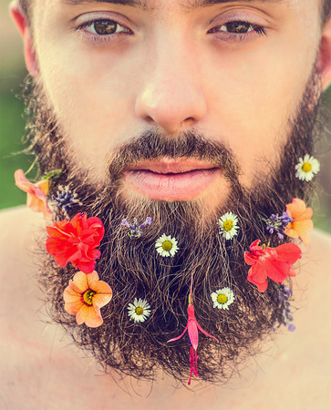 close in: mans face with a beard with flowers in his beard on natural background, close up