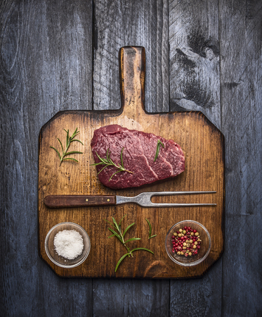 raw ribeye steak on a cutting board with a fork, with rosemary salt and pepper on rustic wooden background, top view Фото со стока