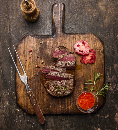 steak grill: roasted ribeye steak sliced on a cutting board with a fork, red sauce, peppers and tomatoes on rustic wooden background, top view
