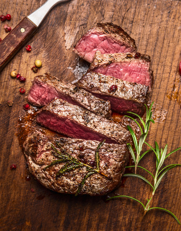 roasted ribeye steak sliced on a cutting board with a fork, rosemary and peppers, top view, close up Stockfoto