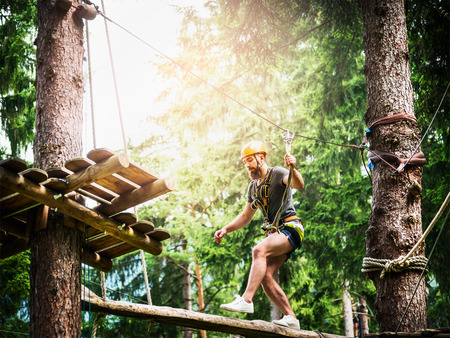 Young  bearded guy is climbing on the rope in climbing forest on beautiful nature bakgrund