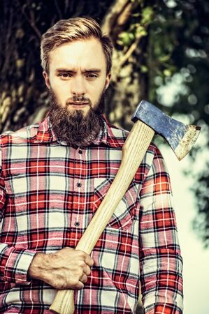 ax man: Bearded young man in checkered shirt holding a old ax on tree nature background, outdoor
