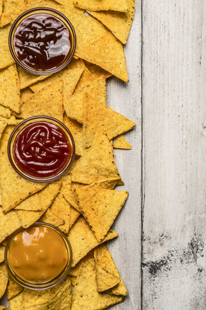 nacho: Mexican nacho chips and colorful dip in glass bowls on white wooden background, top view, vertical border Stock Photo