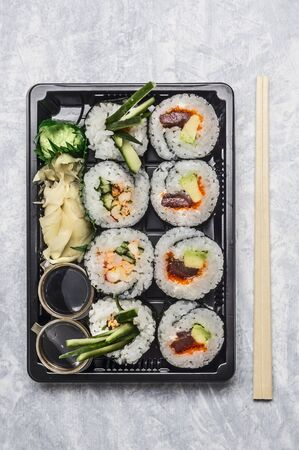 lunch tray: sushi menu in black transportbox or bento box on gray background, top view, close up
