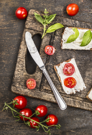 healthy snack: sandwiches with cream cheese, tomatoes and basil for healthy snack on rustic wooden cutting board, top view Stock Photo